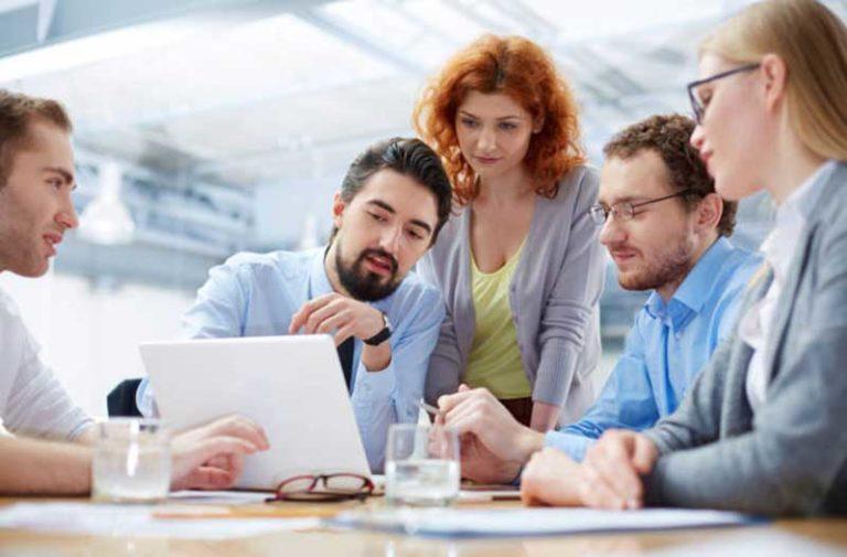 Vijf mensen in een kantoor die naar een laptop kijken en met elkaar praten