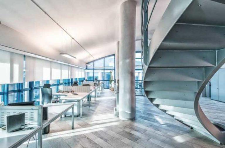 Een helder verlicht kantoor met werkruimten aan de linkerkant en een wenteltrap aan de rechterkant