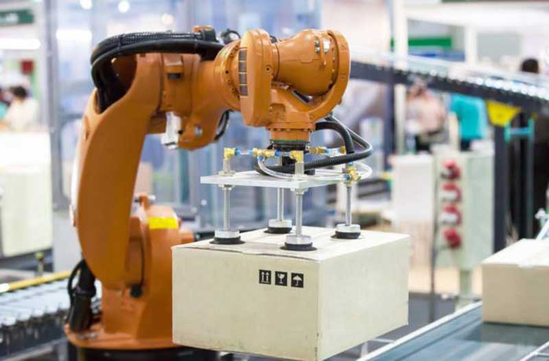 Robotarm pakt pakket op in magazijn