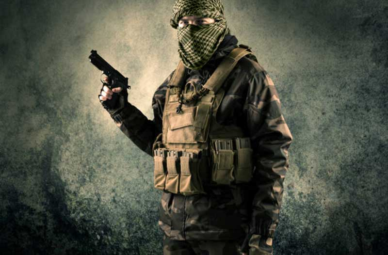 a man with a covered face, holding a gun, and wearing an army vest