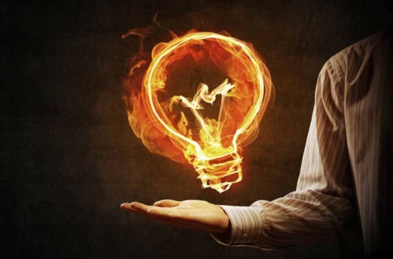 flaming light bulb floating above man's hand