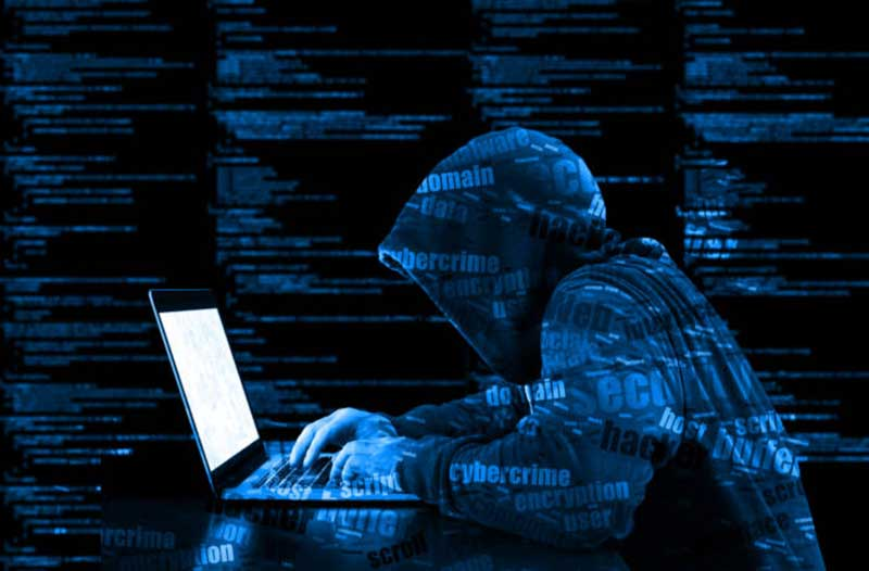 A hacker in a hoodie typing on a laptop, with lines of code in the background