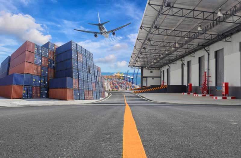 Vliegtuig vliegt boven een scheepswerf met stapels containers