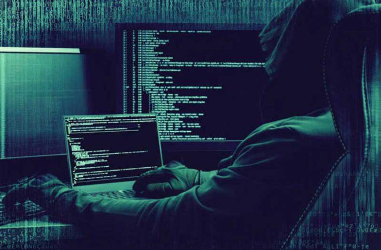 Een hacker met een hoodie zit in een donkere ruimte en kijkt naar een computerscherm met computercode