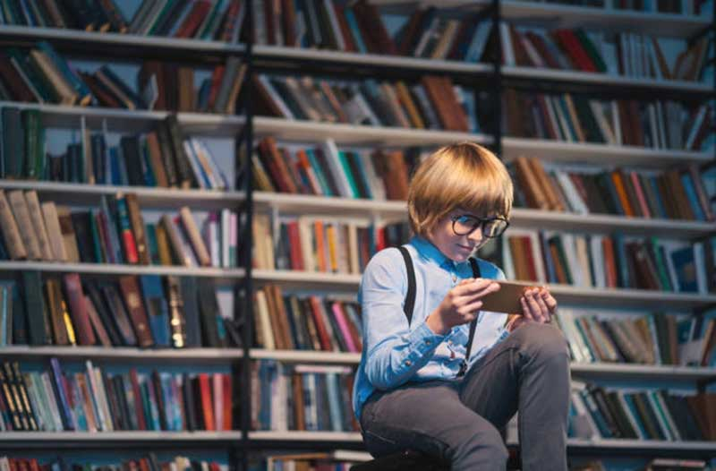 A child sitting in a library looking at a smartphone