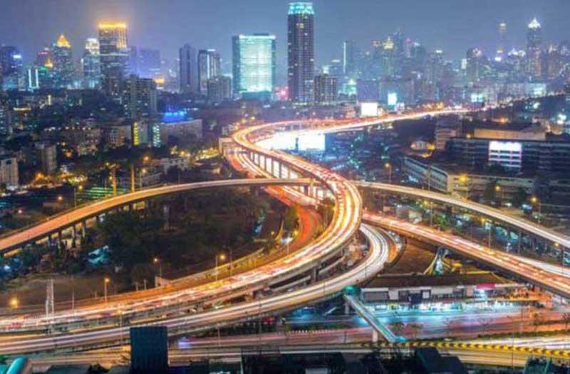 Een verlichte stad bij avond waar verschillende snelwegen doorheen kronkelen