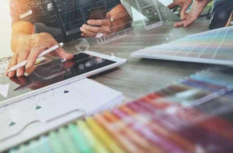 Twee personen zitten aan een tafel met een tablet, laptop, smartphone en een grote doos kleurpotloden