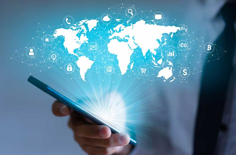 Person holding smartphone with hologram of world map