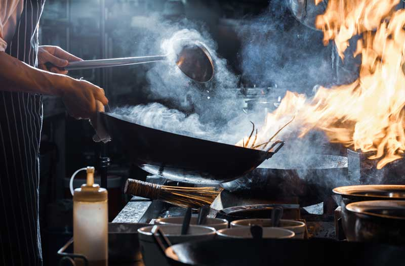 Person preparing food in a frying pan on high heat, causing burning and smoke