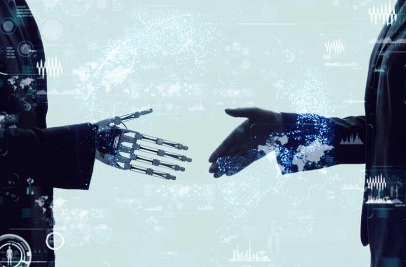 A robot in a suit and a man in a suit about to shake hands