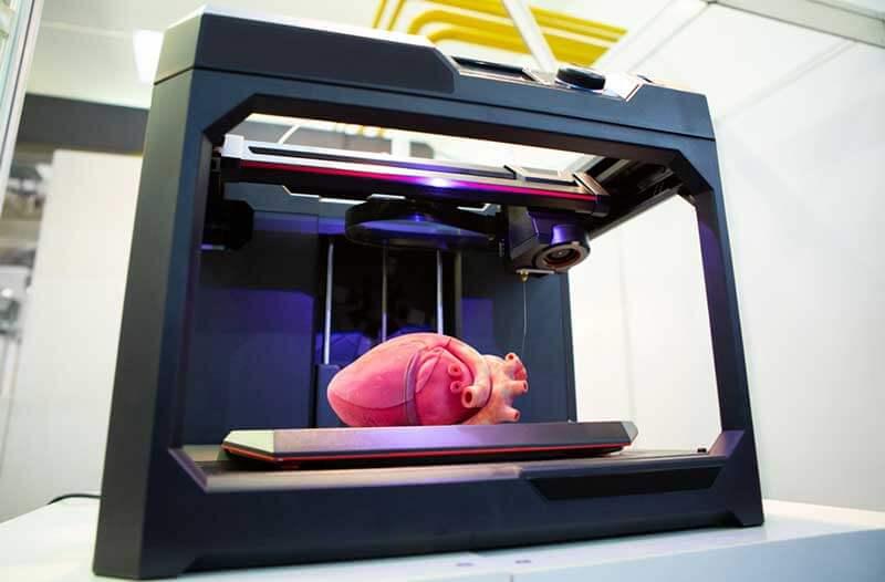 Bioprinter met glazen wanden waarin een roze hart ligt