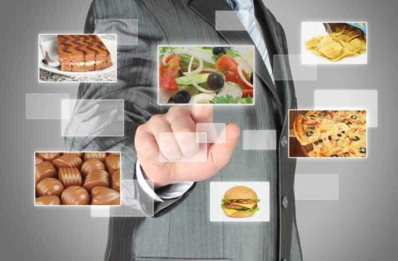 Persoon in pak communiceert met een digitale interface met afbeeldingen van voedsel