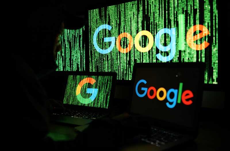 Hacker zit voor diverse computerschermen met binaire code en het Google-logo