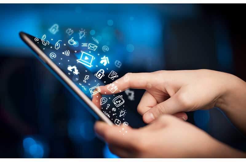 Twee handen typen op een keyboard waarboven verschillende digitale iconen zweven||
