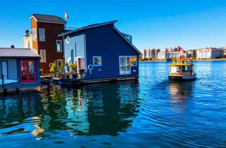Houten huizen in verschillende felle kleuren drijven op het water
