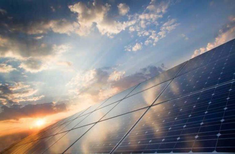 Zonnepanelen gefotografeerd vanaf de grond af, met een zonsondergang op de achtergrond