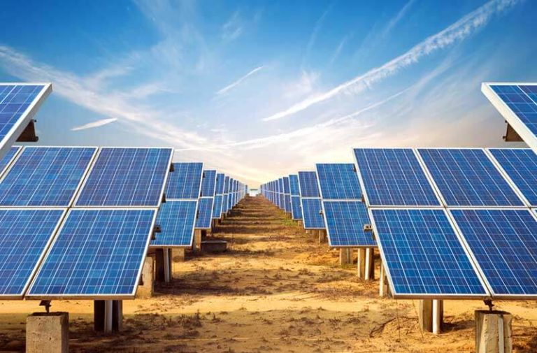 Solar farm with many solar panels in rows under blue sky