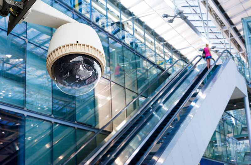 A video surveillance camera in a shopping mall with escalators and large glass walls