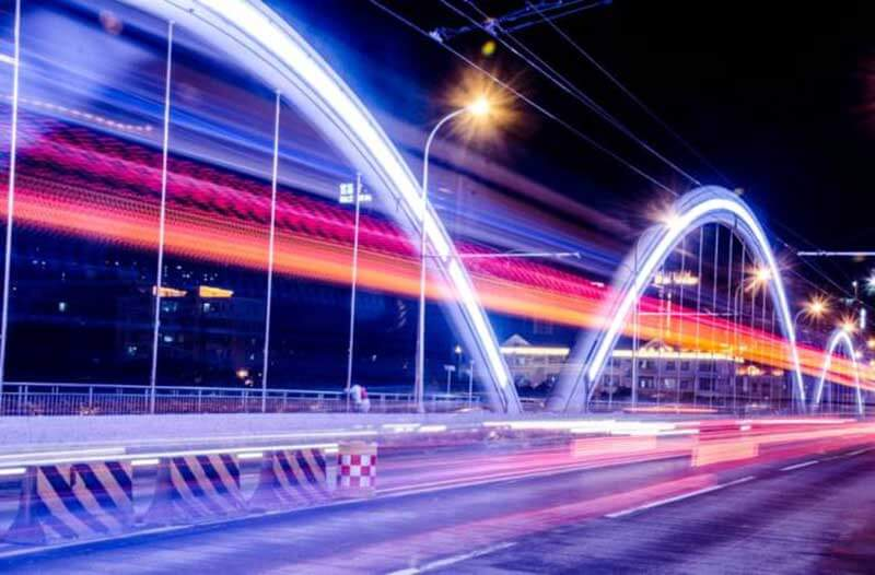 A long exposure photo of a road at night with illuminated arches and neon glowing lines