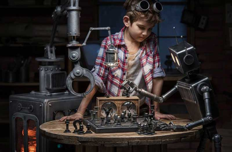 Jongen kijkt naar een schaak-spelende robot in een werkplaats
