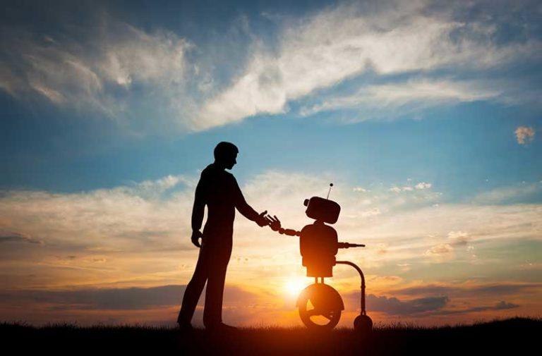 Silhouet van een man die de hand van een robot aanraakt met op de achtergrond de ondergaande zon in een blauwe hemel met wolken