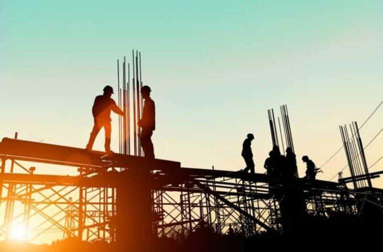 Arbeiders op een steiger op een bouwplaats bij zonsondergang