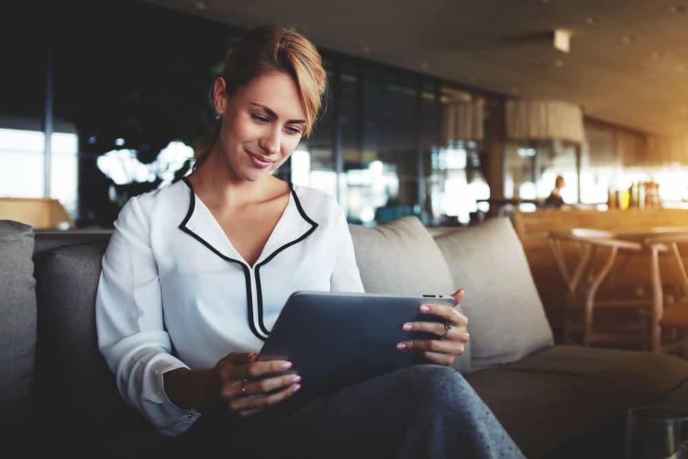 Een blonde vrouw met een wit shirt zit op een bank en kijkt op haar tablet|Sanoma zet co-creatie in voor nieuwe iPad apps