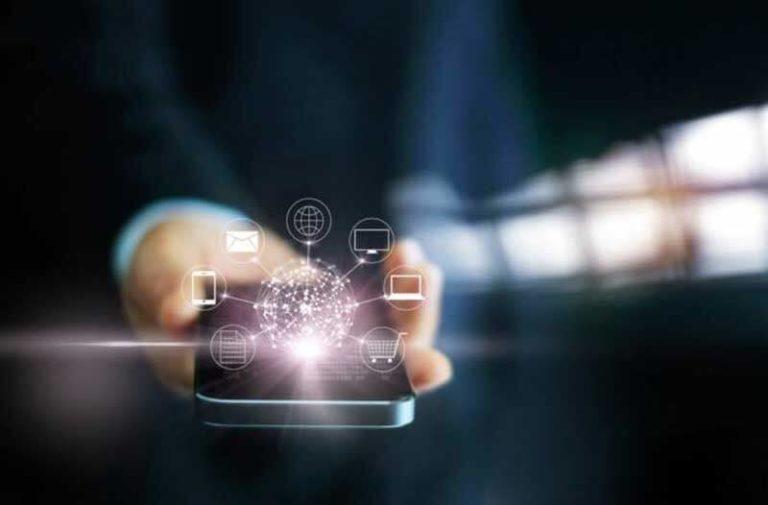 Een hand met een smartphone waarboven holografische pictogrammen zweven