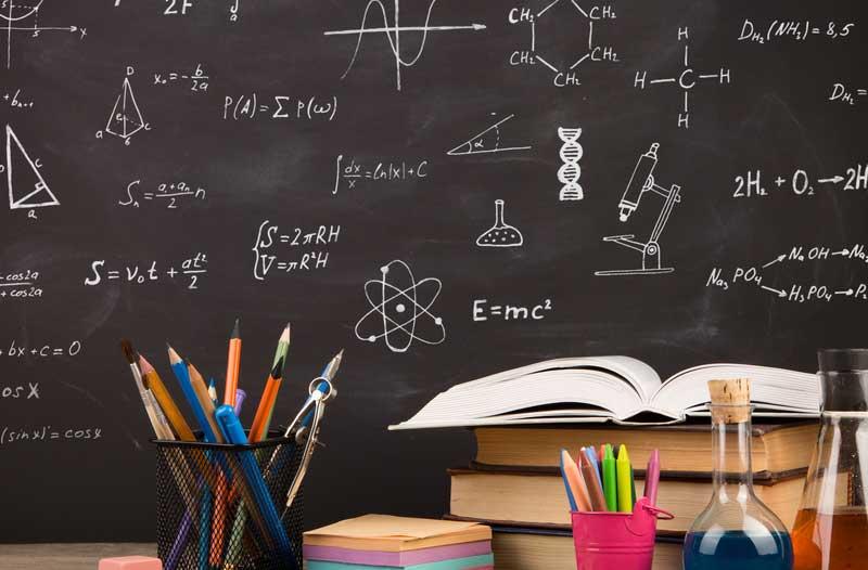 Bureau met boeken en potloden en een schoolbord op de achtergrond