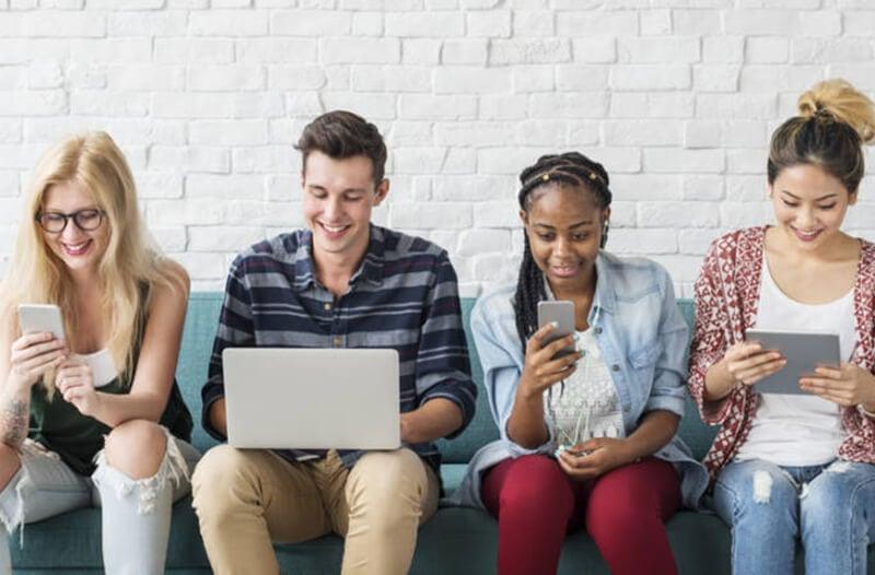 Vier personen zitten op een bank en iedereen houdt een mobiel apparaat vast
