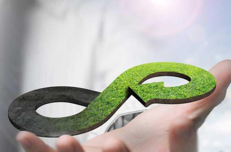 Hand die groen symbool van de circulaire economie vasthoudt