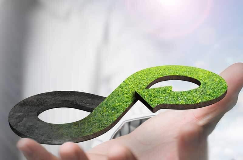 Hand holding green circular economy symbol