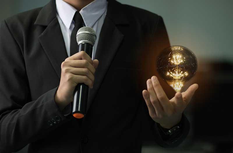 Een man in pak met in de ene hand een microfoon en boven de andere hand een zwevende gloeilamp