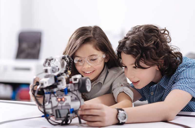 Two kids interacting with a robotic device