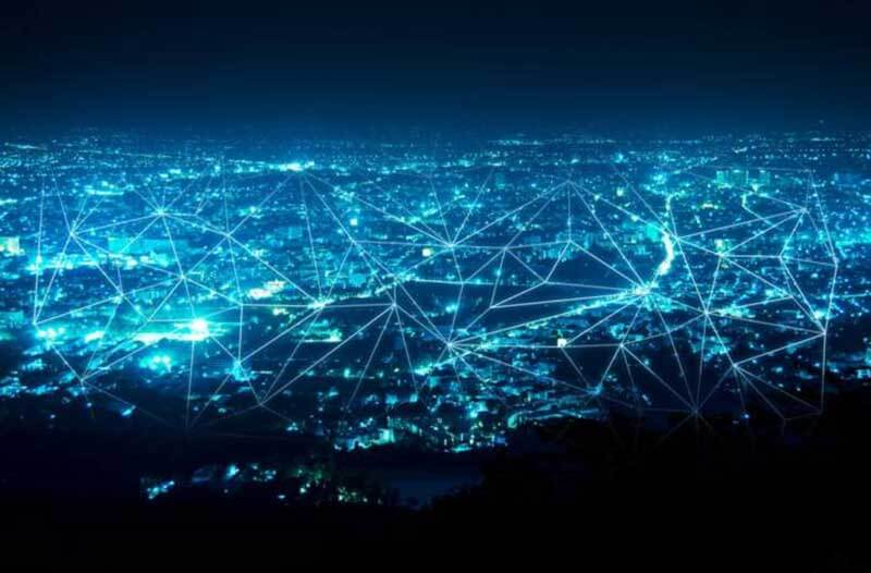 A city at night overlaid by a network of lines and dots