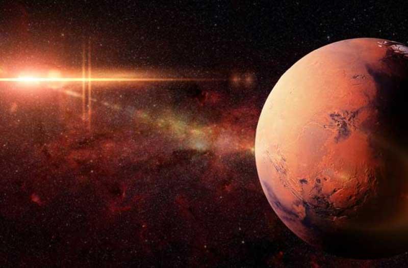 Een rode planeet in de ruimte met op de achtergrond een ster met een rode gloed