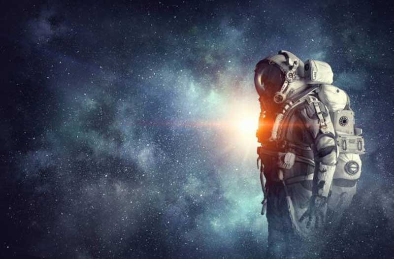 Man wearing an astronaut suit standing in space with a lot of stars in the background