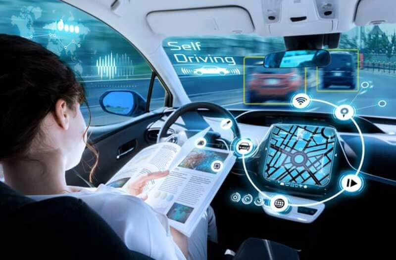 Een vrouw zit achter het stuur van een zelfrijdende auto een boek te lezen