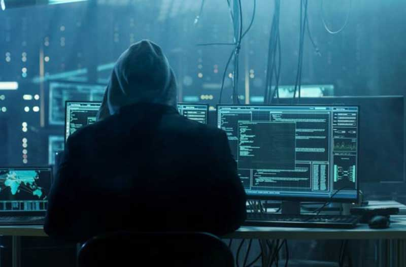 Back view of a man wearing a hoodie sitting in front of computer screens and cables