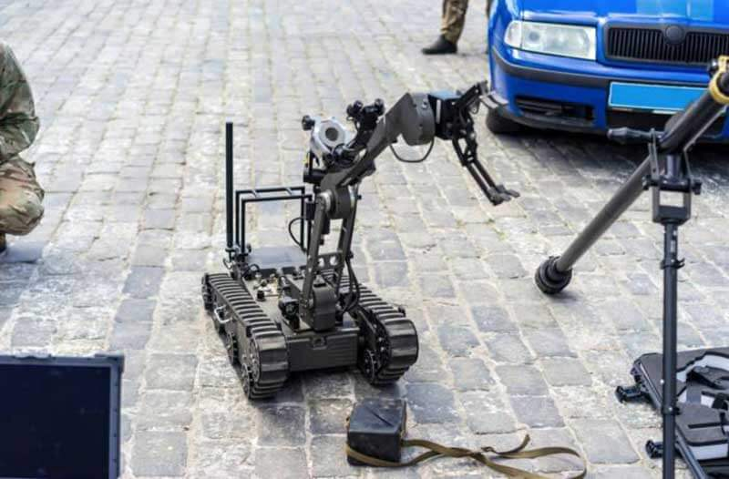 A bomb-disposal robot called Taurus standing in front of a blue car