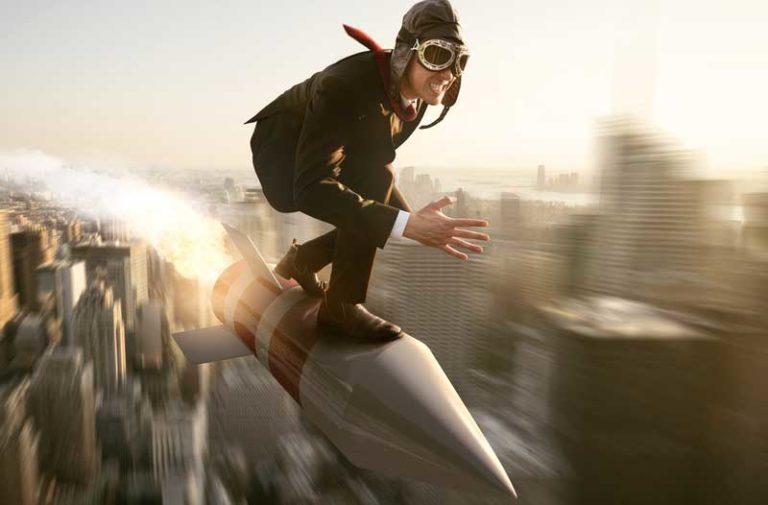 Persoon met vliegeniersmuts en vliegeniersbril op een raket die boven een stad vliegt