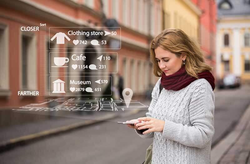 Een vrouw op straat houdt een smartphone vast waarboven digitale iconen zweven