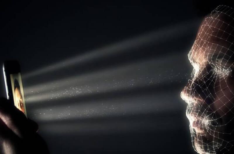 Persoon in een donkere ruimte houdt een smartphone vast die lijnen en stippen op zijn gezicht projecteert