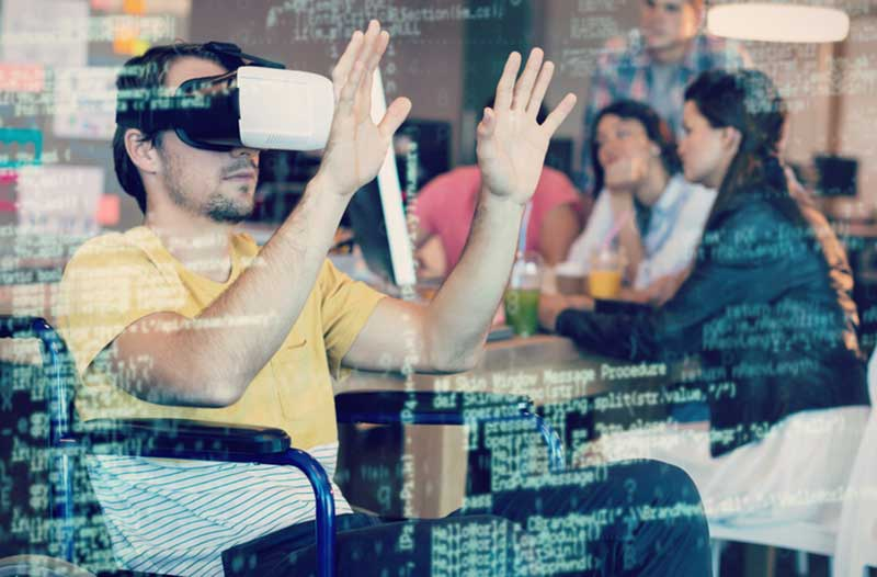 Man with VR headset sitting in a chair holding his hands in front of his face