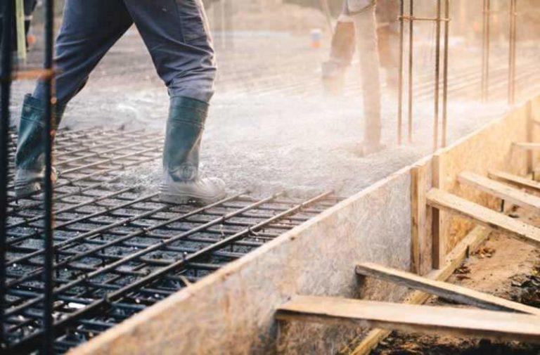 De benen van twee bouwvakkers die beton gieten voor een fundering
