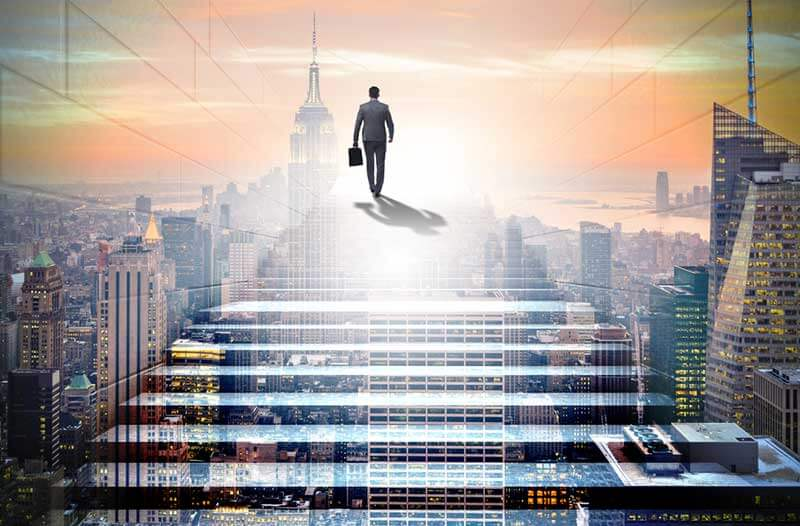 Man in pak loopt een virtuele trap op die boven een futuristische stad zweeft