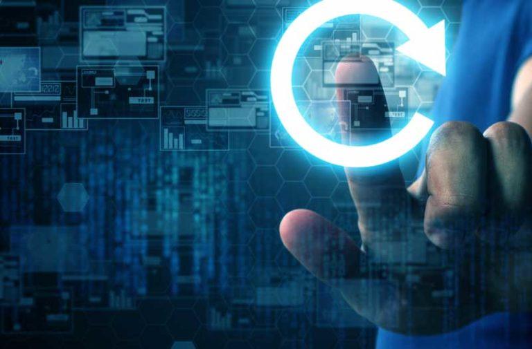 Een close-upfoto van een hand die een cirkelvormig pijlpictogram aanraakt, met grafieken en computercode op de achtergrond