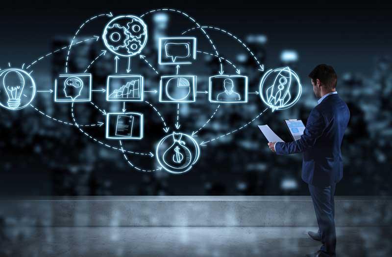 Man in pak met documenten in zijn handen staat voor een groot digitaal scherm met lichtgevende pictogrammen