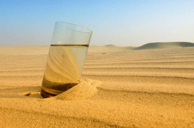Glass of water in desert sand with blue sky