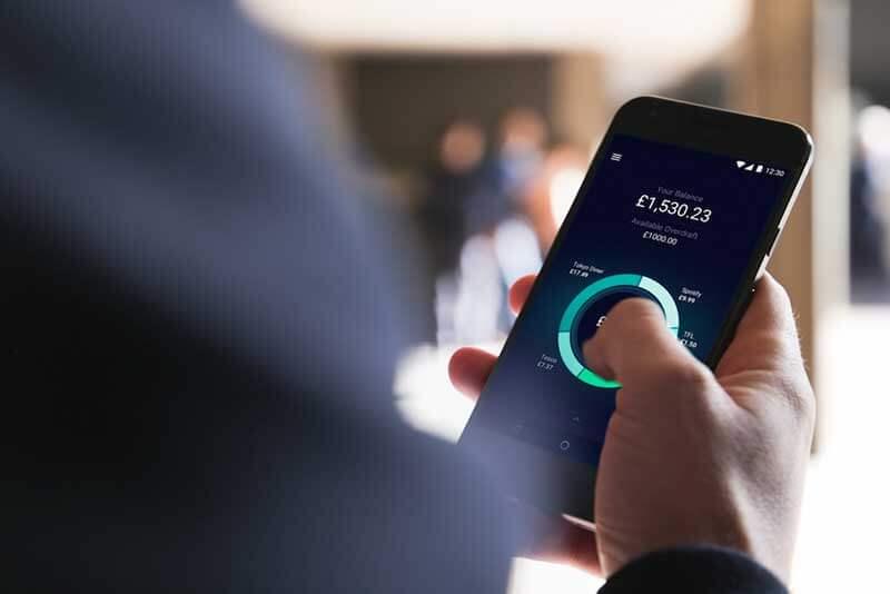 Een hand met een smartphone tegen een achtergrond met pictogrammen en infographics||||Fintech startups are making it big in finance|